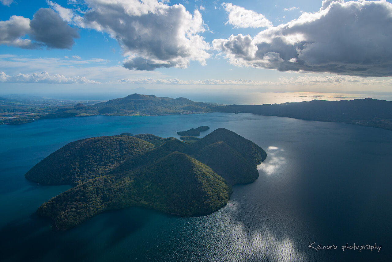 Lake Toya in October, taken from a helicopter in the sky above Nakajima, the island located in the middle of Lake Toya. Visible on the left hand side are Mt. Usu and Mt. Showa Shinzan, which were formed by volcanic eruptions.   ©Noro Keiichi