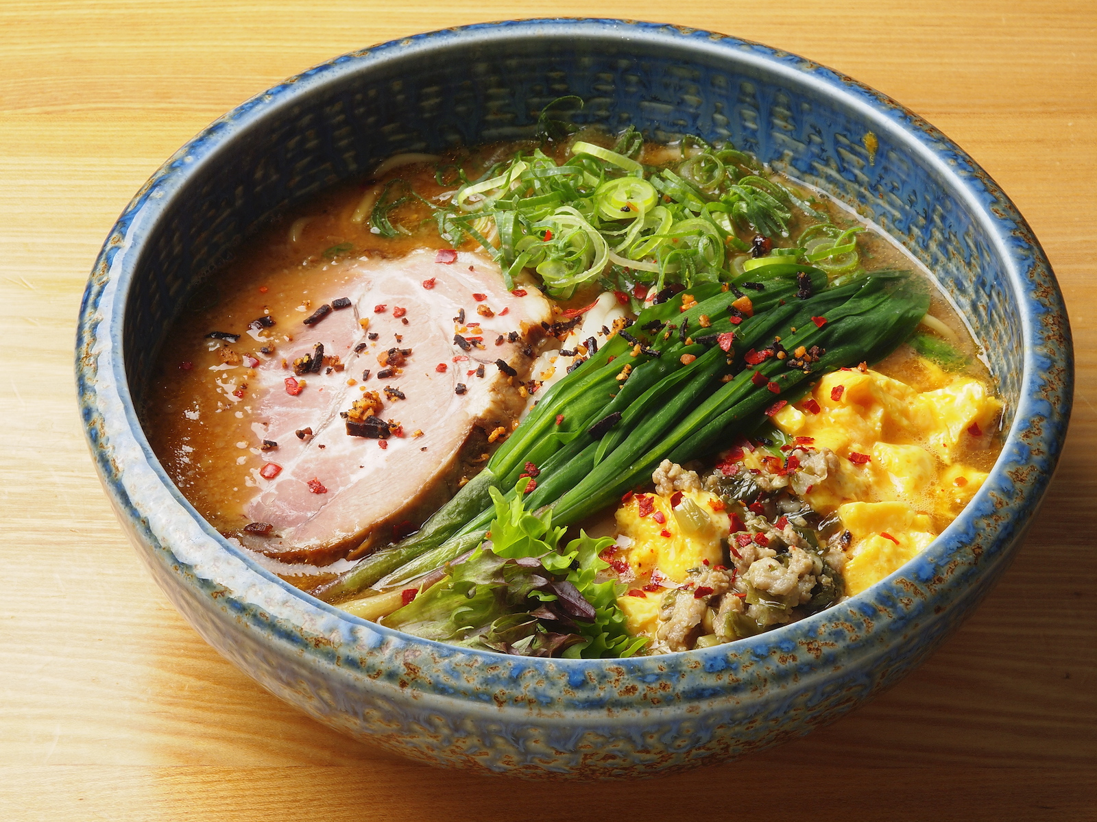 """The prominently featured alpine leek goes great with the slightly salted scrambled egg in the """"bowl that lift your spirits"""" at Ramen Sapporo Ichiryuan."""