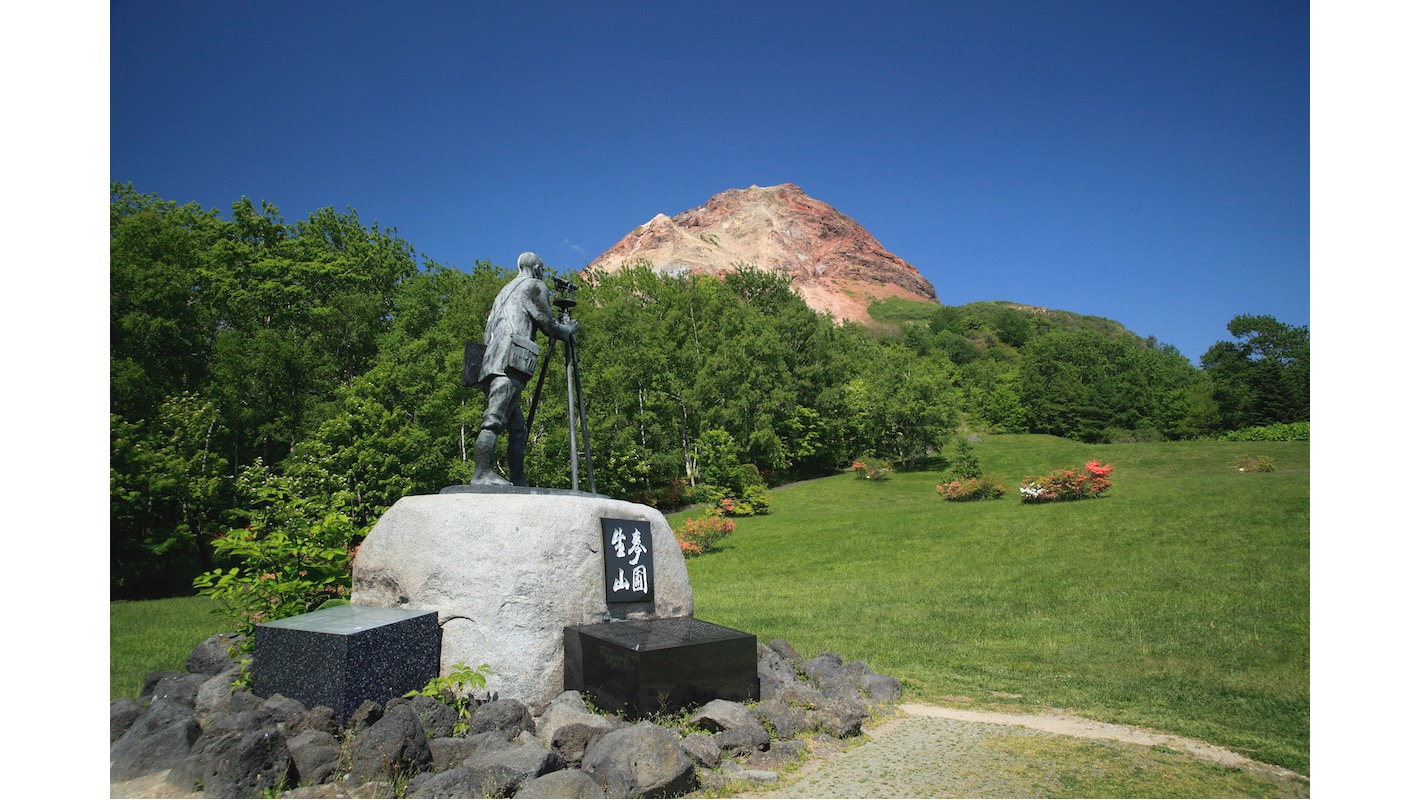 Showa Shinzan, which is designated a Special Natural Monument. At the mountain's foot, a statue dedicated to Masao Mimatsu, who spent many years of his life recording relevant data with regards to Showa Shinzan's formation. photo: ©spo/a.collectionRF /amanaimages